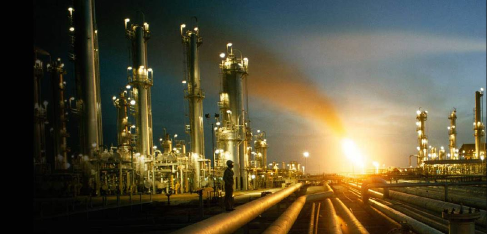 Caribbean Industrial and Agricultural Chemical Services Limited. I worker stands in front of pipes with a glowing fire with smoke trailing into the sky behind and industrial towers to the left.