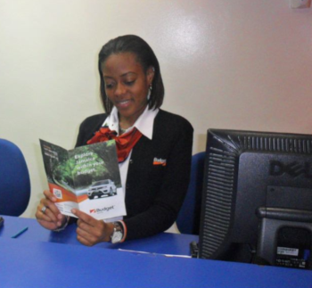Budget Rent a Car Jamaica office with a woman sitting at a desk reading a brochure.