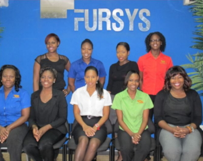 A group of employees in two rows for a photo in front of the name FURSYS.