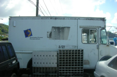 A Grenada Postal Corporation truck parked with two mail holders on the ground next to it.
