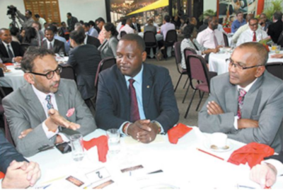 The Honorable Donville O. Inniss, Minister to the Ministry of Industry, International Business, Commerce and Small Business Development meeting with a few gentleman at a dining table. Many other people seated behind them at other tables.