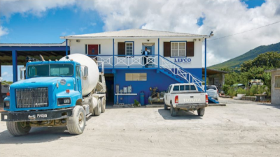 Lefco Equipment Rental. A two story building with Lefco on the side and a Cement truck and regular truck out front with someone on the second story balcony.