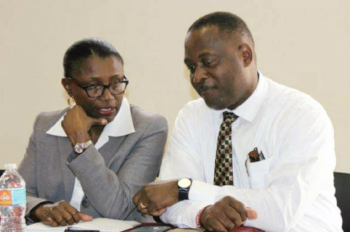 The Honorable Donville 0. Inniss, Minister of Industry sits with a woman in a suit talking.
