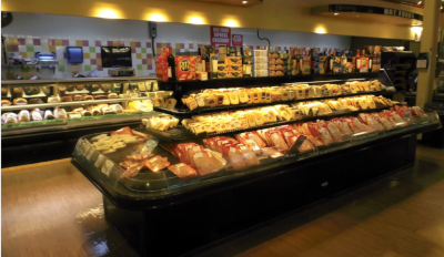 Roadtownwholesale Trading Ltd, a view of a deli with a large selection of meats and cheese on display up front and their deli counter for meats behind.