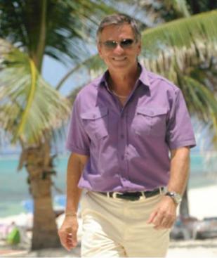 Gaetan Babin, Director of Wyndham Reef Resort walking along the beach.