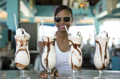 Wyndham Reef Resort, a woman sits with 4 milk shakes in front of her.
