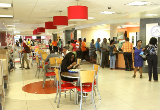 Sky Mall Barbados food court with people sitting at tables down the center eating food. With many more patrons standing in line in front of fast food restaurants to the right.