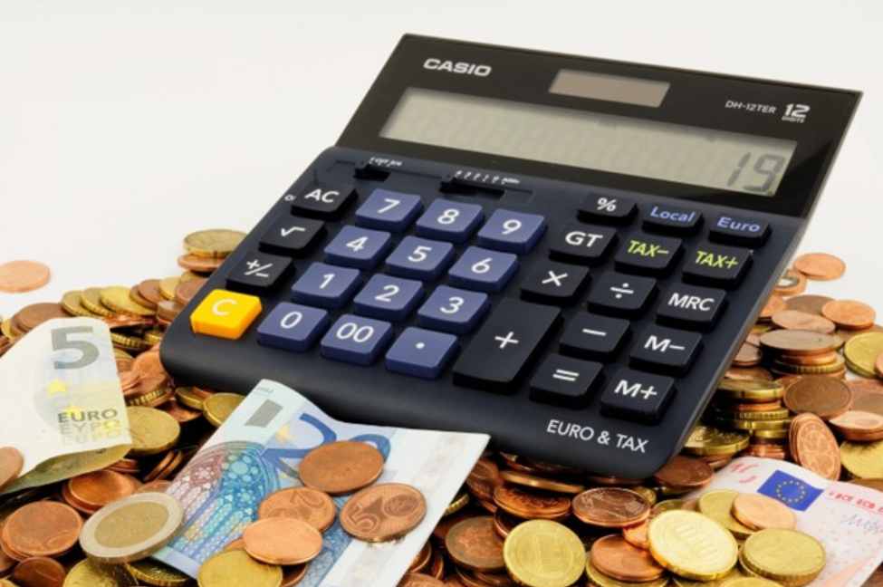 A large calculator sitting atop a pile of euros, both paper and coins.