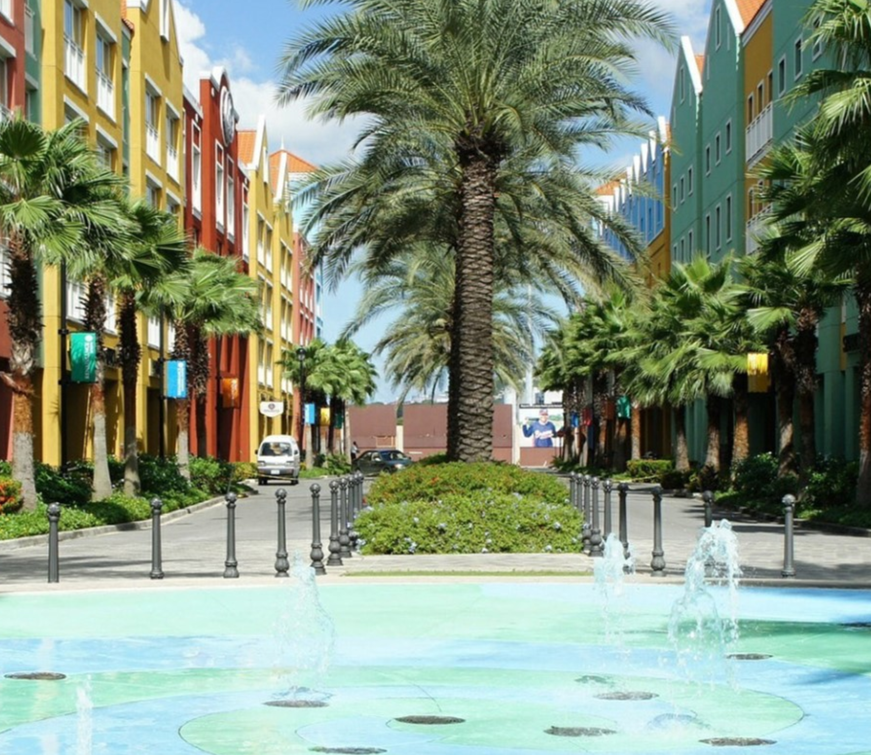 A beautiful street view with bright color buildings of blues, greens, oranges and reds lining both sides of a street with a median. Palms trees lining the street and in the foreground, a blue and cement swirl pattern on the ground with water fountains throughout. Property represented by Crye-Leike Real Estate Services.