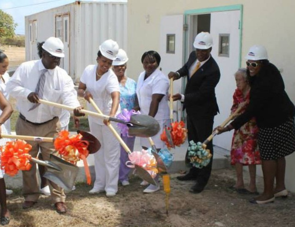 A group of people dressed up wearing hard hats using shovels with bows attached to break ground at a building.