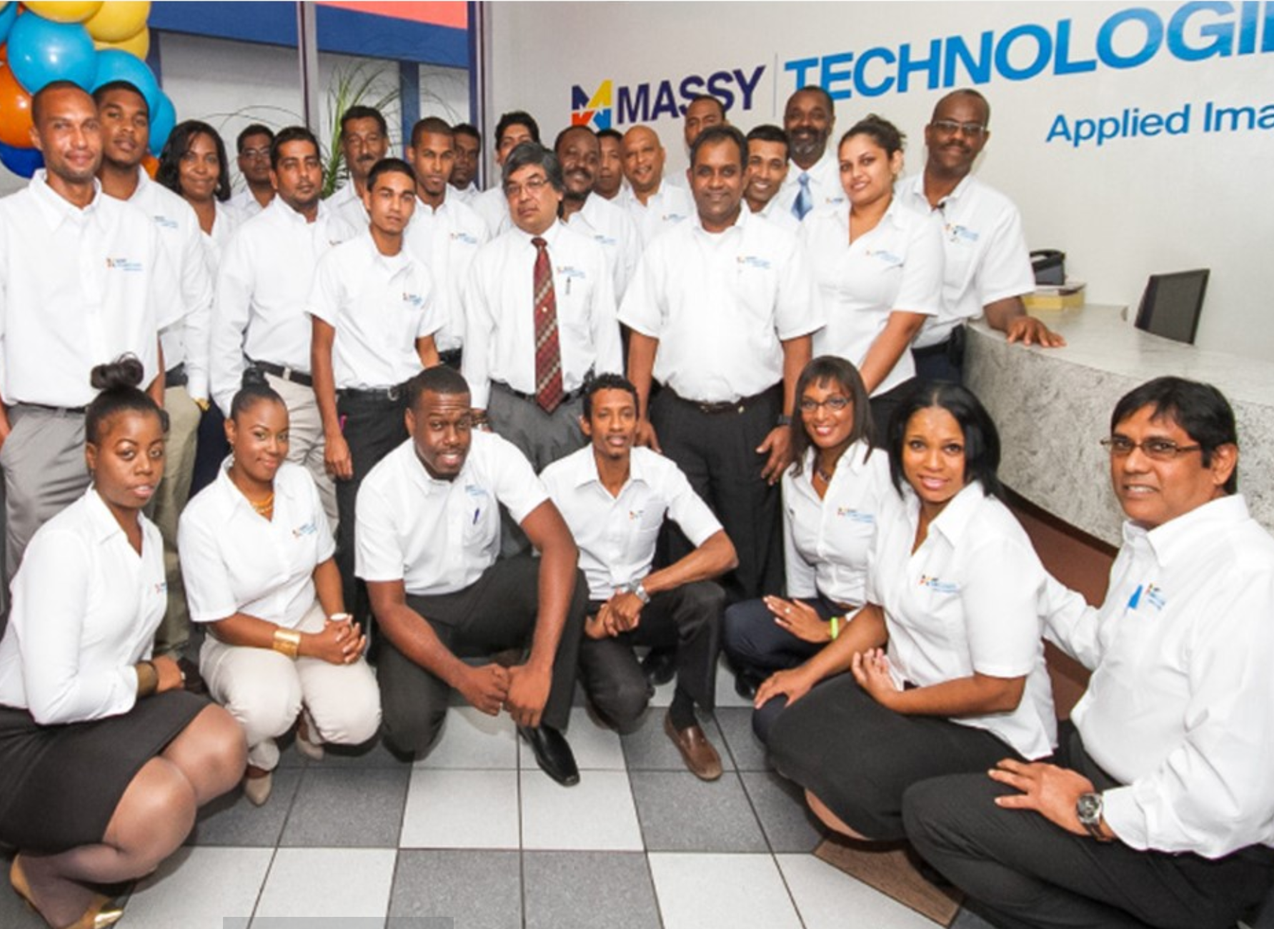 A group photo of Massy Technology employees, back row standing, front row kneeling.