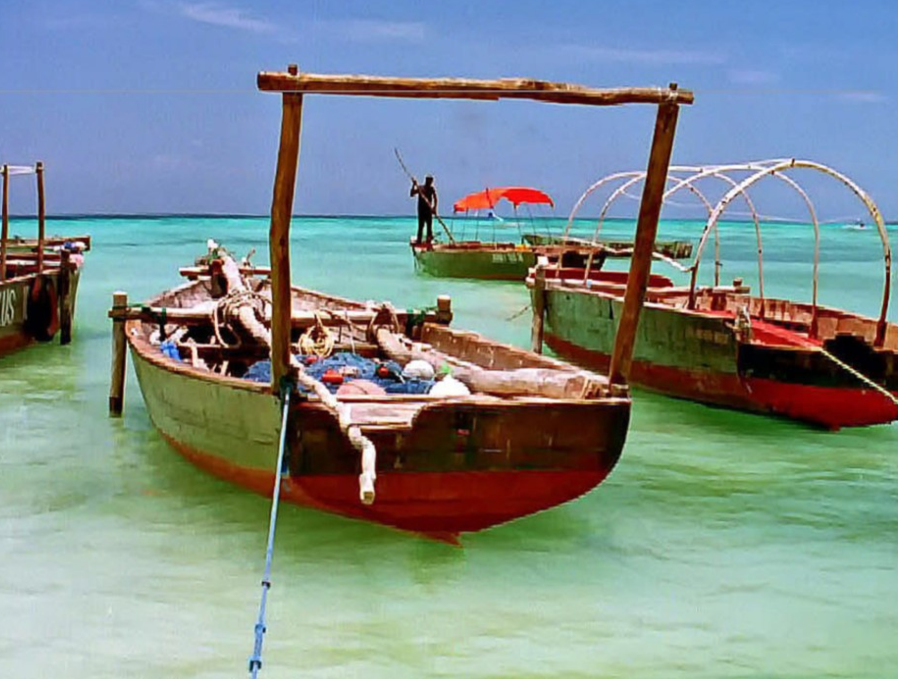 Wooden boats docked in the foreground with one being propelled by a pole in the background.