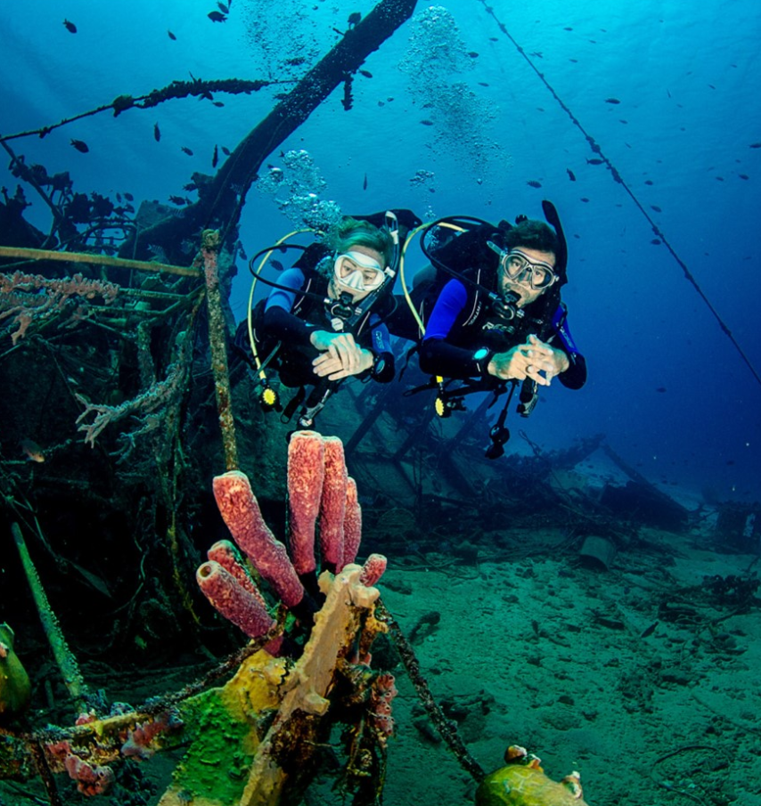 Scuba divers at harbour village beach club in blue water next to a ship wreck with coral.