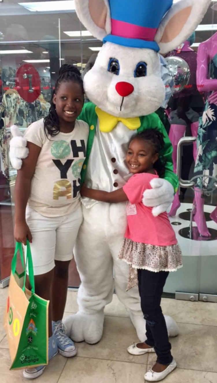 Children hugging and standing with the Easter bunny in front of a storefront at the mall