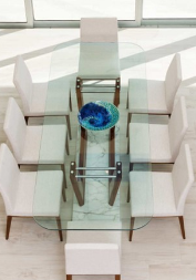 High quality Norstar Group example home showing white chairs around a clear glass table in a well lit room.