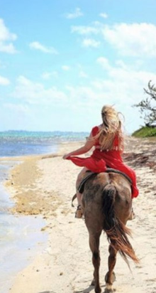 Ministry of District Administration, Tourism and Transport. A woman rides a horse on the beach along the blue waters of the Caribbean.