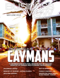 May 2018 cover of business view caribbean showing residential housing buildings with a palm tree in the middle and the sun peaking around it.