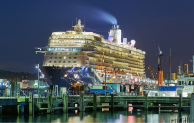 A cruise ship docked at night with lights on.