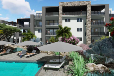Aquarius Caribbean, a new residential project digital mockup showing a large residential building and pool with tables and chairs and landscaping.