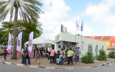 Autobusbedrijf Curaçao. A group of people waiting in line at a bus information center in Otrobanda.