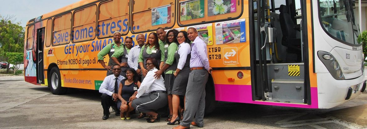 Autobusbedrijf Curaçao employees posing in front of one of their buses for a photo.