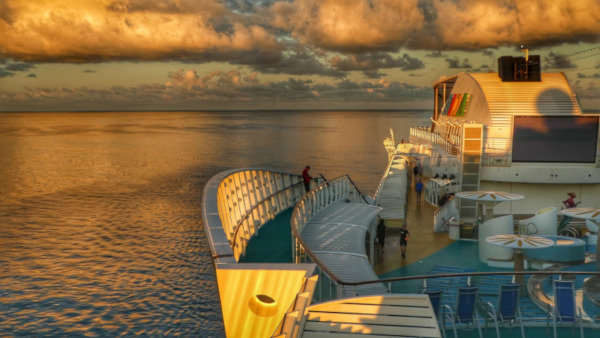 Upper deck of a cruise ship with people walking along it. Puffy clouds and water to the left and behind.