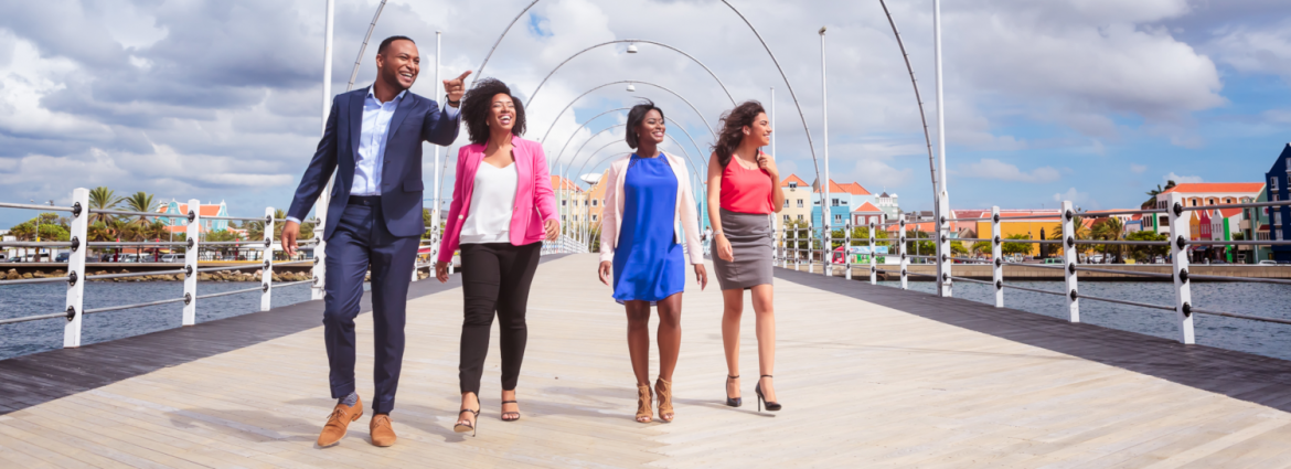 Curacao Hospitality Tourism Association. A man and three women walking on a pier with the man smiling and pointing something out.