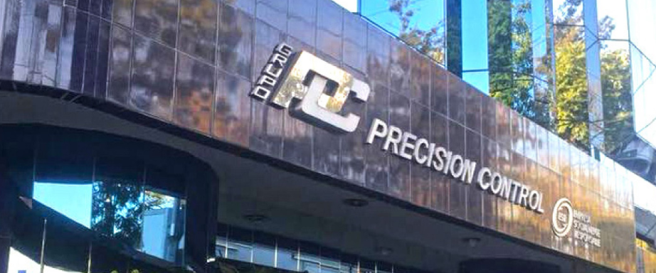 The front of the building showing the sign for Grupo Precision Control.