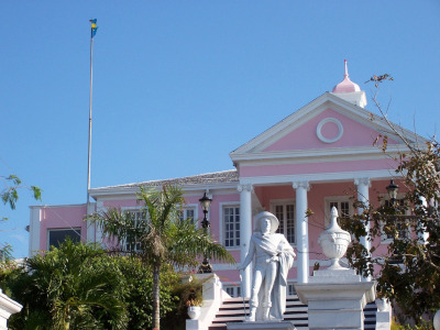 Nassau, Paradise Island. Nassau government building with a flag flying and statue out front.