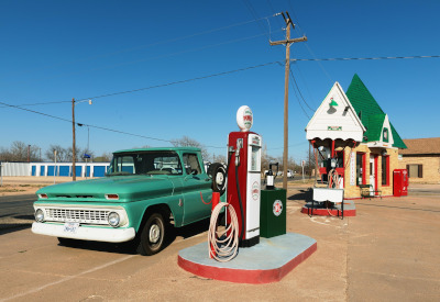 A classic truck pulled up to an old time, glass dome, gasoline pump.