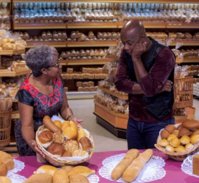 Mangusa Supermarkets; A woman holds up a basket of bread for an onlooking man.