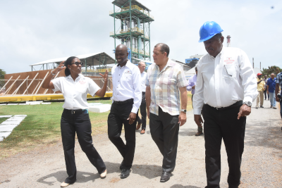 National Rums of Jamaica, 4 people walking and talking at a construction site, one man wearing a blue hard hat.