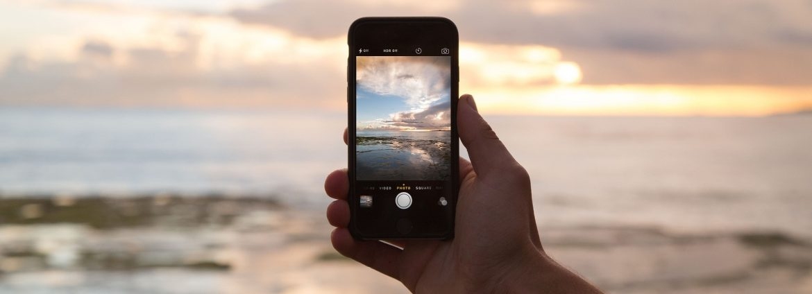 A hand holding a cell phone on a beach with a photo of the beach on the phone.