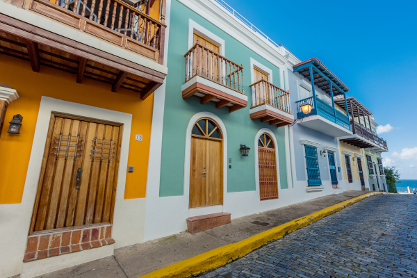 Property Management Inc. Puerto Rico. Colorfully painted houses along a stone paved street.