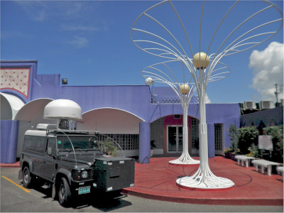 The Spectrum Management Authority of Jamaica, front of their building with a vehicle parked out front that has a communications device on top.