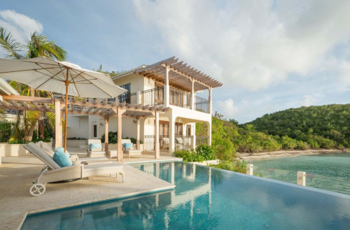 Blue Waters Resort and Spa - Antigua. The back of a house with a pool and ocean in view.