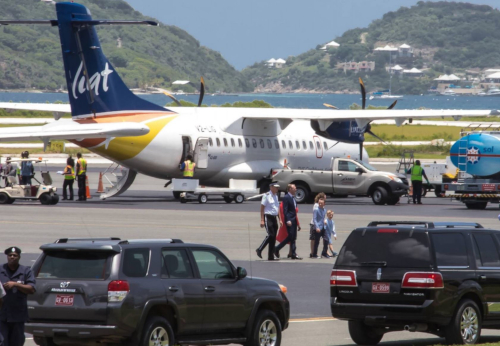 The British Virgin Islands Airports Authority. A plane on a runway with people and cars around.