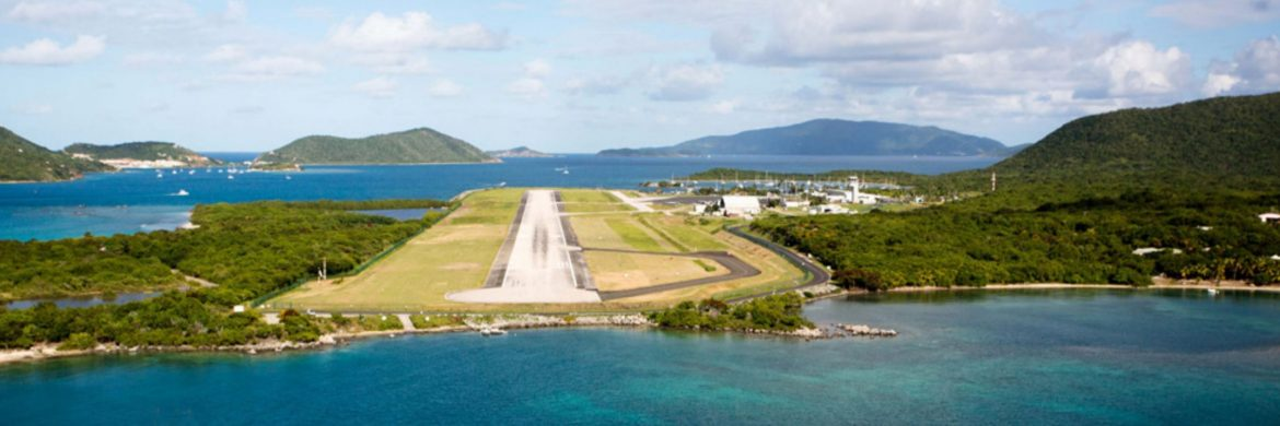 The British Virgin Islands Airports Authority. An airport runway on an island in the Caribbean with other islands in the distance and water around.