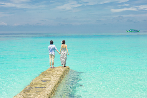 Caribbean Tourism Organization. A beach scene with two people holding hands and standing on a cement dock with algae from being submerged. Bright blue water all around with a boat and clouds in the distance.