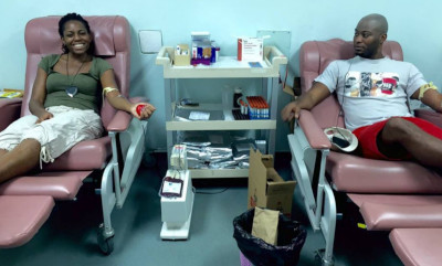 Milton Cato Memorial Hospital, Saint Vincent and the Grenadines. Two people sitting on hospital chairs giving blood.