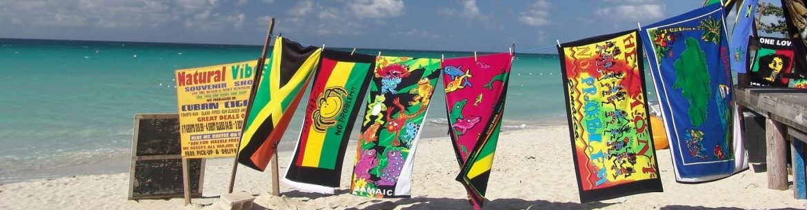A clothing line along a caribbean beach, with beach towels pinned to it outside of a shop to the right.