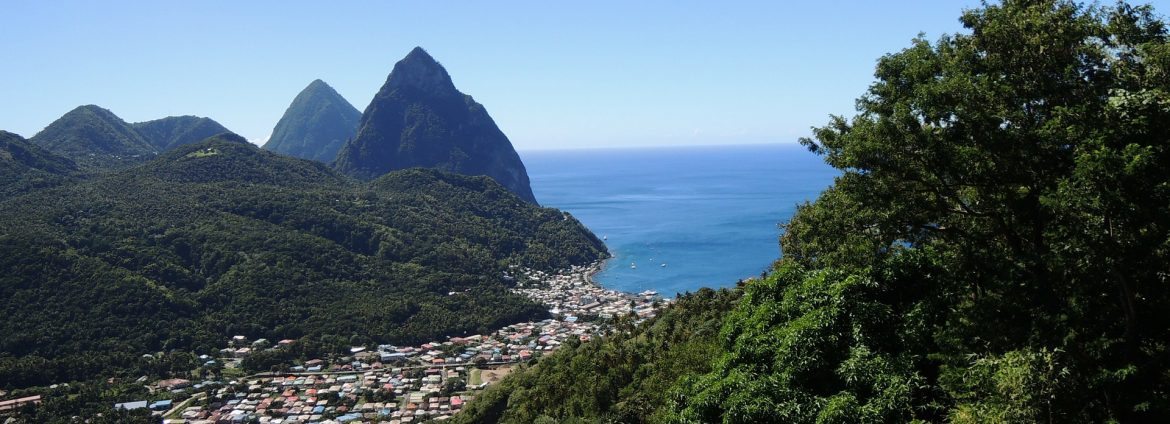 A photo of St. Lucia with the town nested between green hills/mountains in the distance.