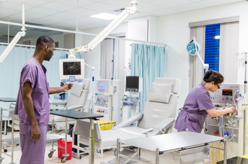 TCI Hospital - Turks and Caicos. Two employees working in a room with patient chairs and other equipment.