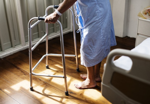 Victoria Hospital St. Lucia. Stock photo of the lower half of a patient using a walker next to their bed.