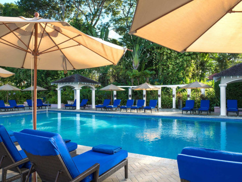 Fairmont Royal Pavillion pool with blue cushioned lounge chairs and umbrellas.