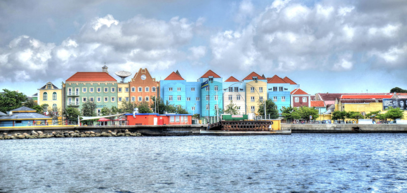 Willemstad ocean view of a row of colorful houses along the water with clouds above. Carribean Hotel & Tourism Association.