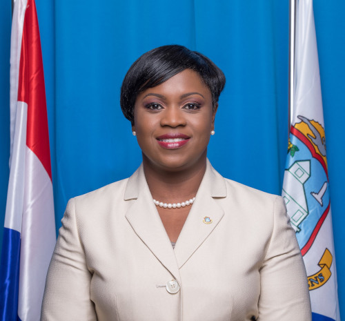 Prime Minister of St. Maarten, Leona Romeo-Marlin standing with two flags behind her.