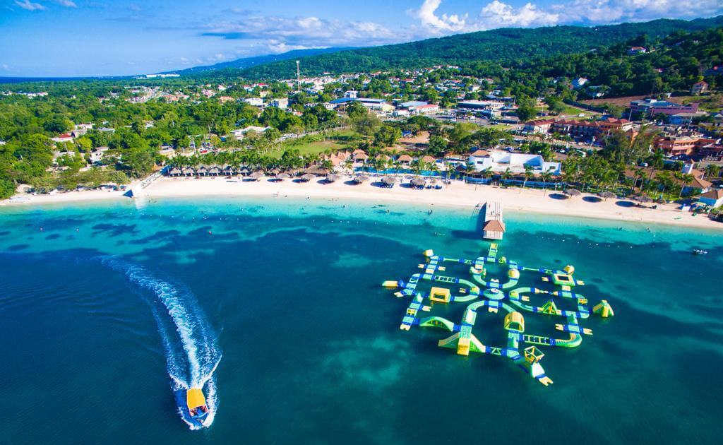Puerto Seco Beach aerial view with a boat leaving the beach by their floating obstacle course.