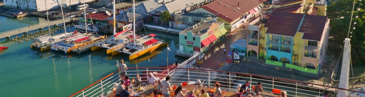 View of a Caribbean town from the back of a ship with people dining on the deck and the town beyond.