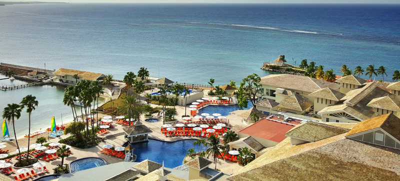 Moon Palace Jamaica, aerial view of the property with palm trees and the ocean stretching to the horizon.